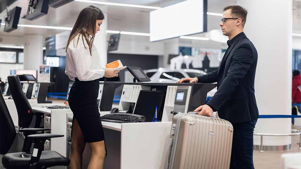 Man at airline front desk with excess baggage